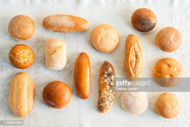 large variety of wholemeal and white bread rolls, overhead view - bun stock pictures, royalty-free photos & images