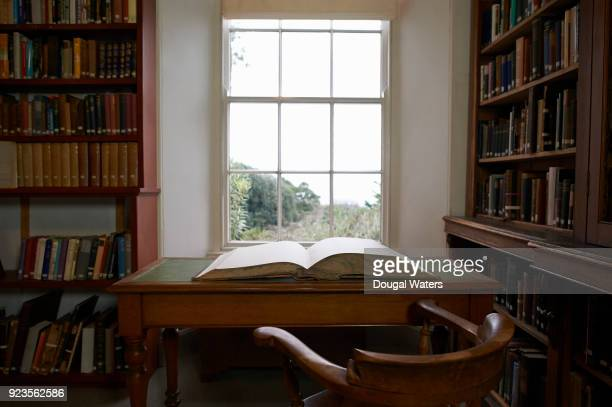 Large vintage book open on library desk in front of window.