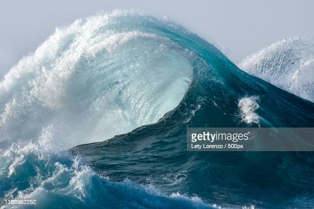 large wave splashing in blue sea - ola fotografías e imágenes de stock