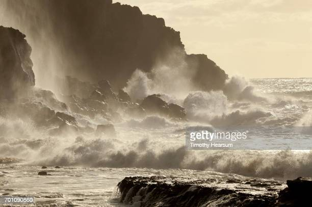 large waves crash against cliff - timothy hearsum stock pictures, royalty-free photos & images