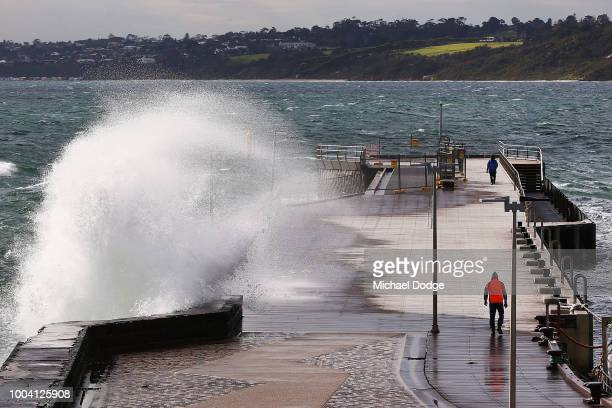 A fisherman prepares as a large wave crashes over Mornington Pier on July 23 2018 in Melbourne Australia A severe weather warning has been issued by...