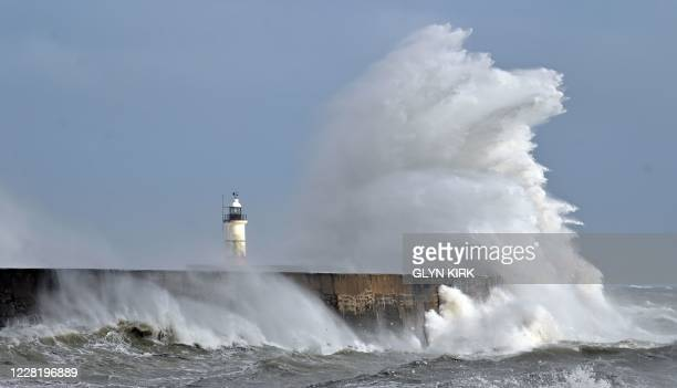Large waves crash over the harbour wall and Newhaven Lighthouse on the south coast of England on August 25, 2020. - Wind gusts of 70mph are expected...