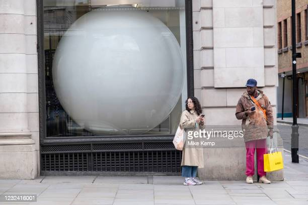 Large white ball in the window of a building in Mayfair on 12th April 2021 in London, United Kingdom. This huge scale sphere interacts with passing...