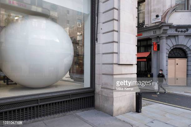 Large white ball in the window of a building in Mayfair on 28th January 2021 in London, United Kingdom. This huge scale sphere interacts with passing...