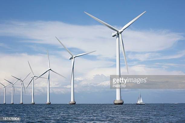 large white windmills in the sea with a sailboat - windenergie stockfoto's en -beelden