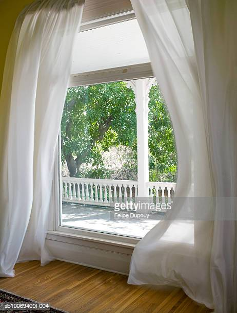 Large window with billowing curtains, view out over porch