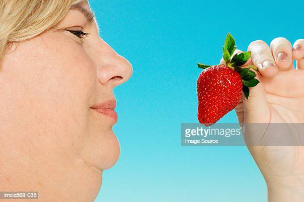 Large woman looking at strawberry