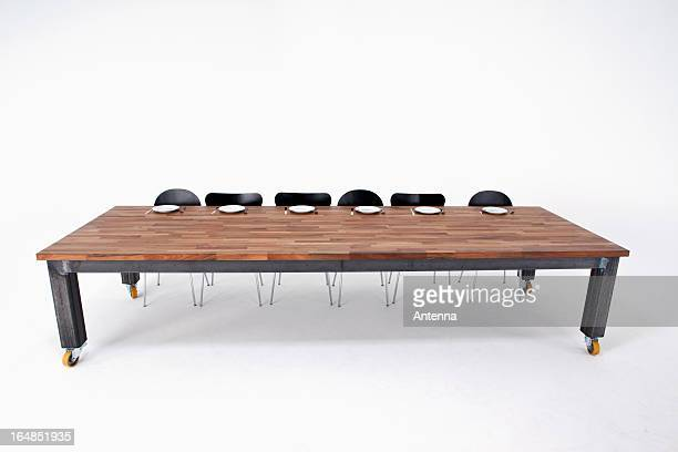 A large wood table with six chairs and six empty place settings