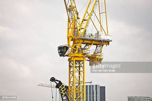 large yellow crane against grey sky - eric van den brulle stock pictures, royalty-free photos & images