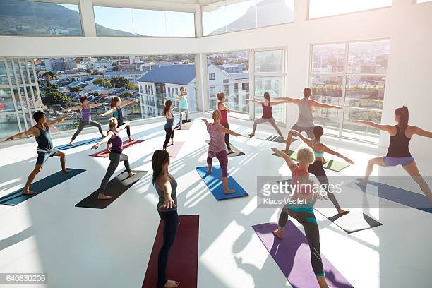 Large yoga class strecthing arms out
