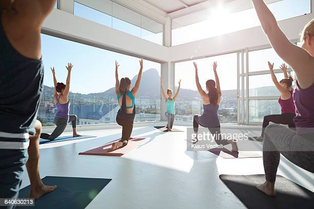 Large yoga class strecthing arms up