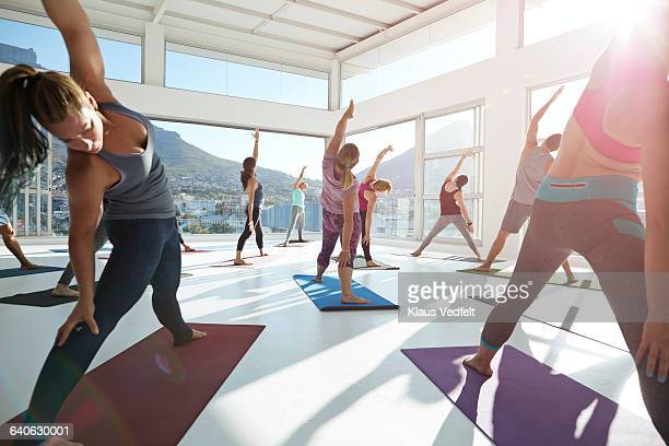 large yoga class stretching - woman straddling man stock pictures, royalty-free photos & images