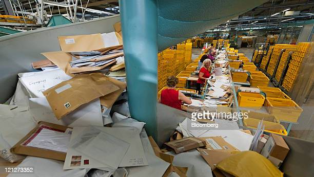 Larger items of mail descend from a chute to be postmarked by hand at Deutsche Post AG's sorting facility in Munich Germany on Tuesday Aug 16 2011...