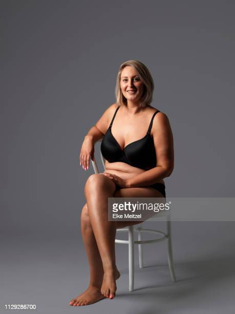 larger woman in underwear sitting on a chair - chubby legs stock photos and pictures