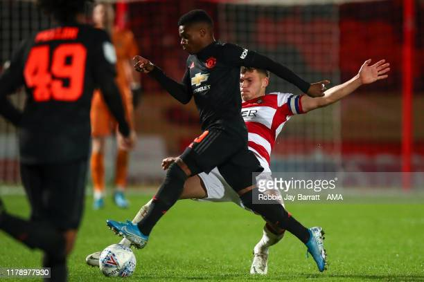 Largie Ramazani of Manchester United U21 and Joe Wright of Doncaster Rovers during the Leasingcom Trophy match fixture between Doncaster Rovers and...