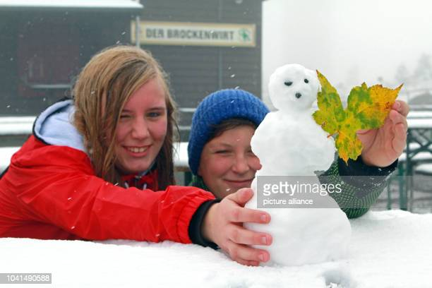Larissa and Johannes build a tiny snowman on Brocken Mountain in Schierke Germany 10 October 2013 A low pressure area brought the first snow this...