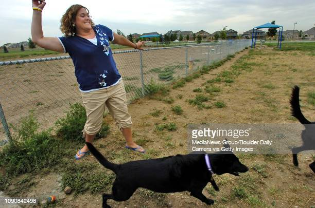 Larissa Malone throws a chunk of wood on Monday for her Labrador mixes Allie left and Baily at the Broomfield dog park temporarily located within the...
