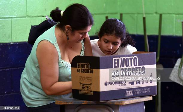 Lariza Salmeron watches her mother Mariela Cervantes as she prepares to cast her vote at a polling station set up at Carlos Sanabria elementary...