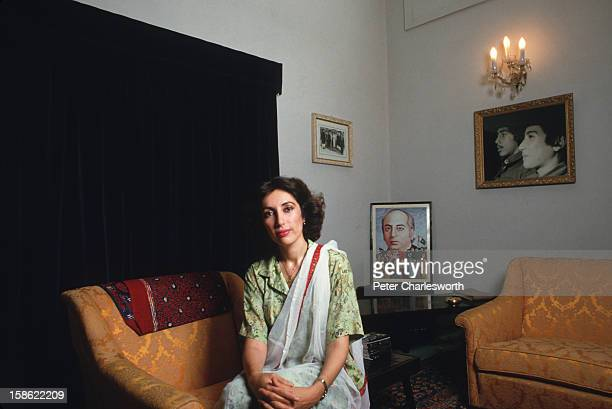 Benazir Bhutto poses for a photograph in her family's residence in Larkarna Behind her is a picture of her father Zulfikar Ali Bhutto former...