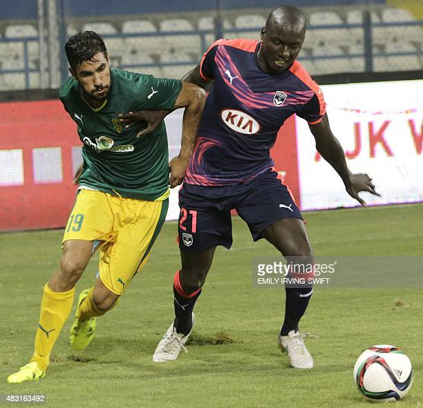 AEK Larnaca's Nestor Mytidis and Bordeaux's Cedric Yambere compete for the ball during their UEFA Europa League football match at the Antonis...