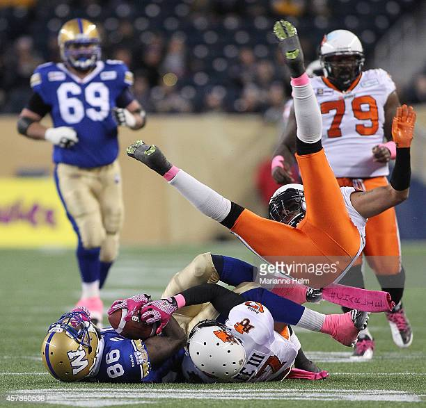 R LaRose of the BC Lions flies over Justin Wilson of the Winnipeg Blue Bombers and TJ Lee in first half action in a CFL game at Investors Group Field...