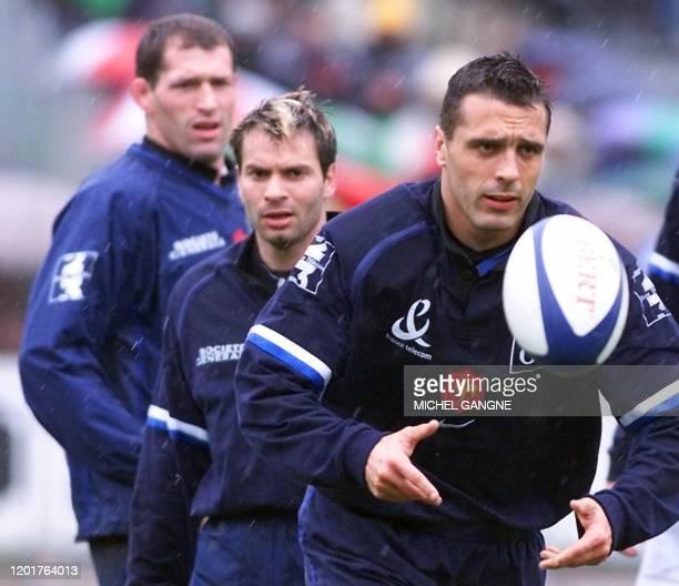l'arrière français Sébastien Viars s'entraîne sous les yeux du 3ème ligne Olivier Magne G et de l'ailier Christophe Dominici le 28 mars 2001 au stade...