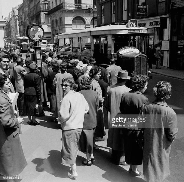 A l'arrêt 'Bourse' les voyageurs très nombreux attendent aux arrêts d'autobus à Paris France le 27 mai 1957