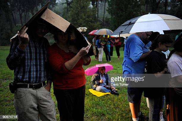 Larry and Kathy Skinner take cover under cardboard as rain pours down during a memorial service for Dirty Dancing star Patrick Swayze September 19...