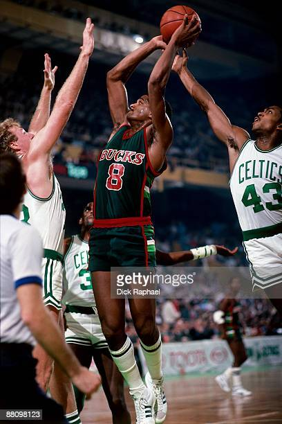 Larry Bird and Gerald Henderson of the Boston Celtics converge on defense against Marques Johnson of the Milwaukee Bucks during a game played in 1984...