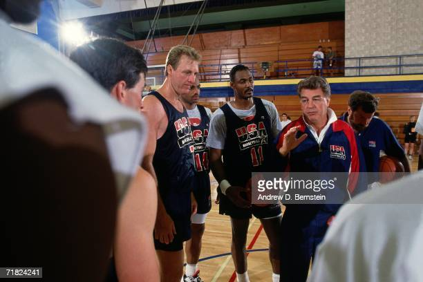 Larry Bird and Karl Malone of the United States National Team listen to head coach Chuck Daly while at practice during the1992 Summer Olympics in...