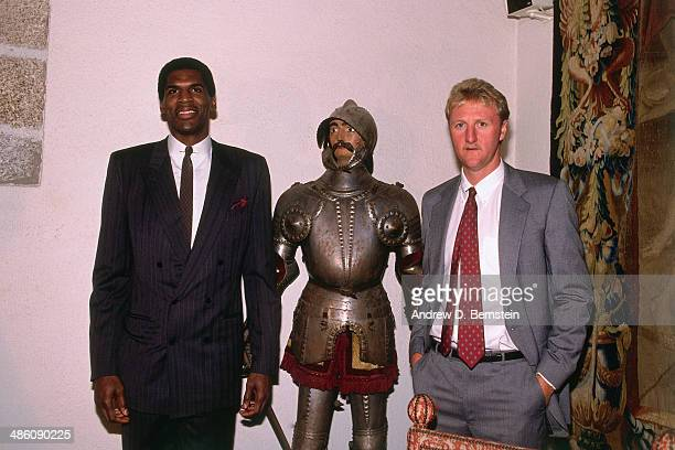 Larry Bird and Robert Parish of the Boston Celtics pose with a statue of a knight during a visit to Castle of los Mendoza during the 1988 McDonald's...