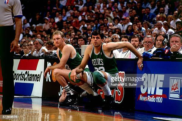 Larry Bird and teammate Kevin McHale of the Boston Celtics wait at the scorers table during a game against the Detroit pistons circa 1991 at the...