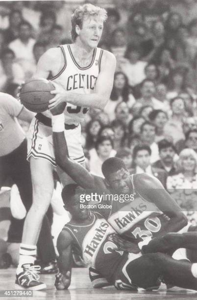 Larry Bird controls the ball after battling with Dominique Wilkins and Tree Rollins