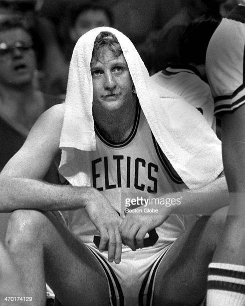Larry Bird is soaking with sweat and covers his head with a towel trying to stay cool in the hot Boston Garden as the Boston Celtics play the Los...