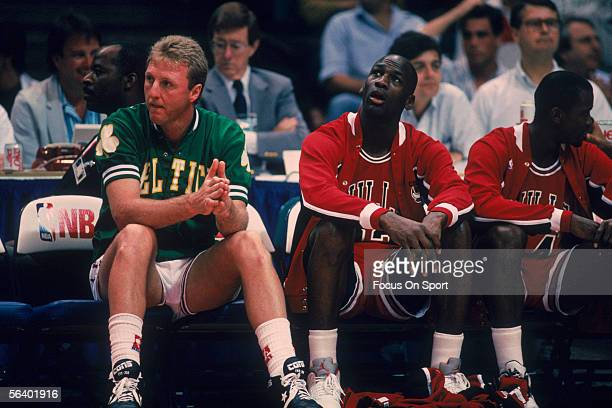 Larry Bird of the Boston Celtics and Michael Jordan of the Chicago Bulls sit on a bench circa 1990 during an NBA AllStar game