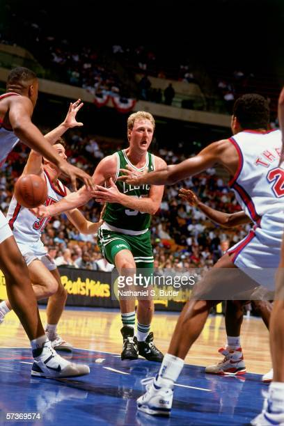 Larry Bird of the Boston Celtics attempts to pass against Reggie Theus of the New Jersey Nets during a game circa 1990 at the Brendan Byrne Arena in...
