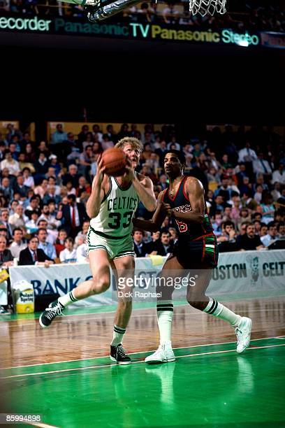 Larry Bird of the Boston Celtics drives against Marques Johnson of the Milwaukee Bucks during a game played in 1983 at the Boston Garden in Boston...