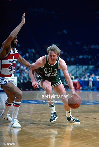 Larry Bird of the Boston Celtics drives on Greg Ballard of the Washington Bullets during an NBA basketball game circa 1985 at the Capital Center in...