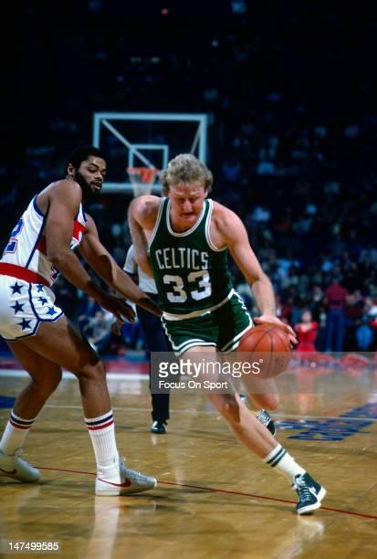 Larry Bird of the Boston Celtics drives on Greg Ballard of the Washington Bullets during an NBA basketball game circa 1983 at the Capital Center in...