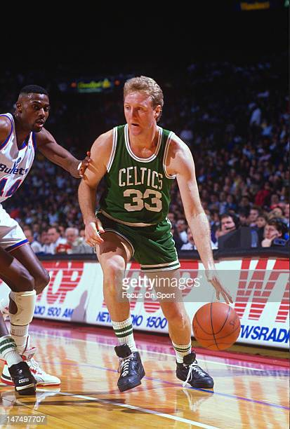 Larry Bird of the Boston Celtics drives on Harvey Grant of the Washington Bullets during an NBA basketball game circa 1989 at the Capital Center in...