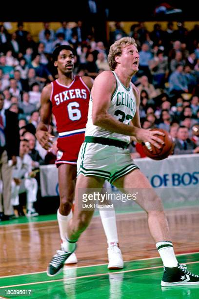 Larry Bird of the Boston Celtics drives to the basket against Julius Erving of the Philadelphia 76ers during a game circa 1984 at the Boston Garden...