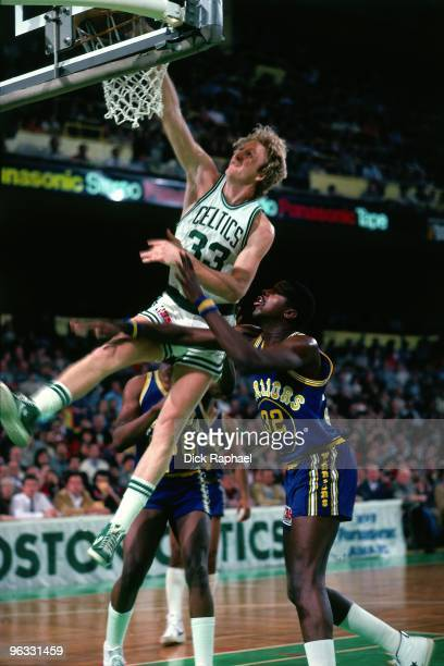 Larry Bird of the Boston Celtics dunks against Rickey Brown of the Golden State Warriors during a game played in 1980 at the Boston Garden in Boston...