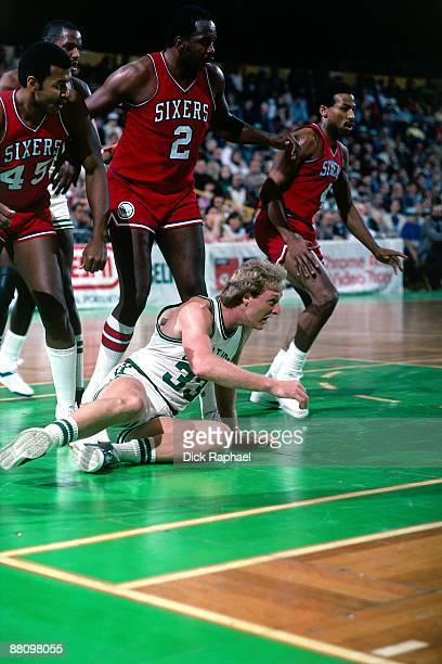 Larry Bird of the Boston Celtics goes down in front of Moses Malone of the Philadelphia 76ers during a game played in 1984 at the Boston Garden in...