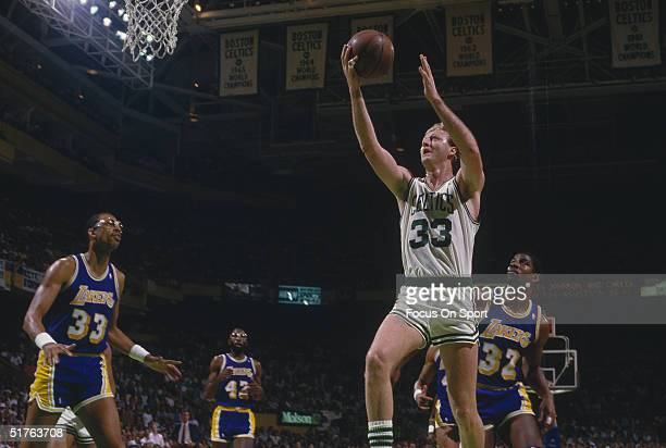 Larry Bird of the Boston Celtics goes for a layup as Kareem Abdul-Jabbar and Magic Johnson of the Los Angeles Lakers watch Bird's shot during during...