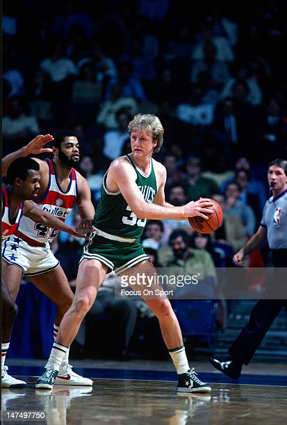 Larry Bird of the Boston Celtics looking to pass over Frank Johnson and Greg Ballard of the Washington Bullets during an NBA basketball game circa...
