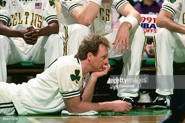 Larry Bird of the Boston Celtics looks on from the floor near the bench area during the 1991 NBA Playoffs at the Boston Garden circa 1991 in Boston...