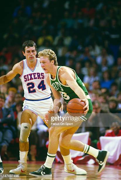 Larry Bird of the Boston Celtics looks to drive on Bobby Jones of the Philadelphia 76ers during an NBA basketball game circa 1984 at The Spectrum in...