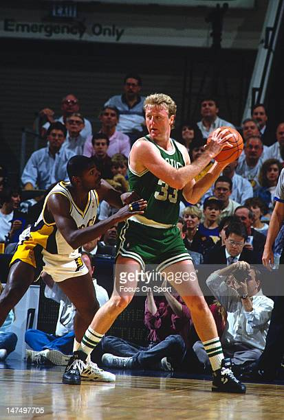 Larry Bird of the Boston Celtics looks to put a move on an Indiana Pacers defender during an NBA basketball game circa 1991 at Market Square Arena in...