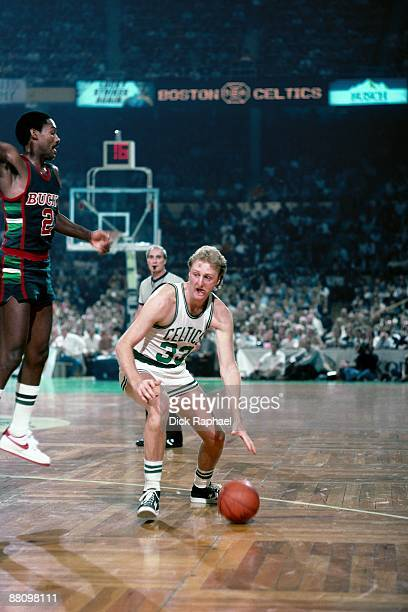 Larry Bird of the Boston Celtics moves the ball up court against Junior Bridgeman of the Milwaukee Bucks during a game played in 1984 at the Boston...
