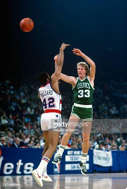 Larry Bird of the Boston Celtics passes the ball over Greg Ballard of the Washington Bullets during an NBA basketball game circa 1983 at the Capital...